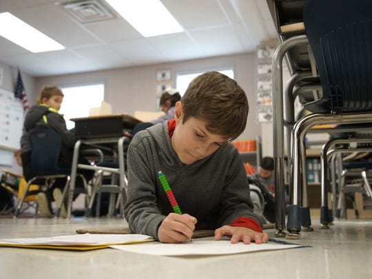 Nine-year-old Alex Barnett, a fourth-grader at Cedar Lane Elementary School, lays on the floor of modular classroom next to his desk working on a social studies assignment.