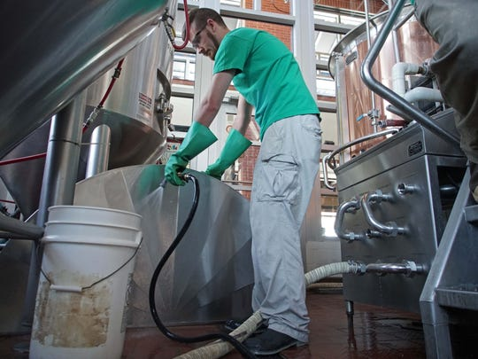 Warren Skopowski, a senior food science major at the University of Delaware, cleans the lids from a mash tun at Iron Hill Brewery as part of his internship.