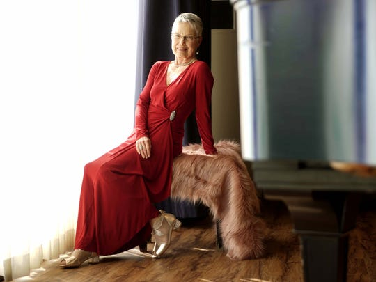 Pat Goodman wears a red gown with crystal brooch at waist from Nordstrom with her short Mongolian lamb vest in a soft pink.
