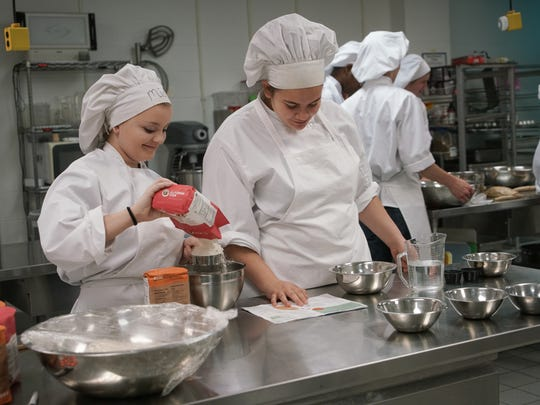 Mia Stout, 16, left, and classmate Destiny Farraday, 17, both juniors in Lindsay Baker's food prep class at Middletown High School, measure ingredients to make bread that will be sent to the Delaware Food Bank for Easter.