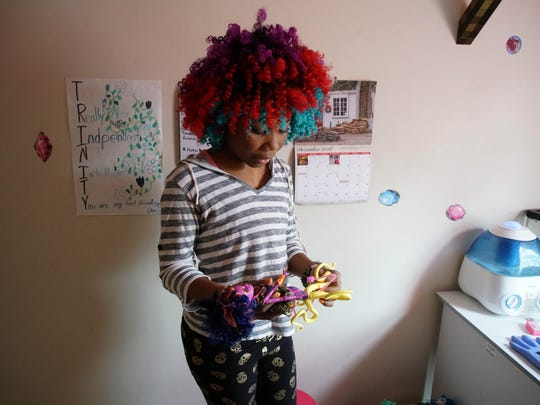 13 year-old Trinity Neal plays with one her dolls in her bedroom.