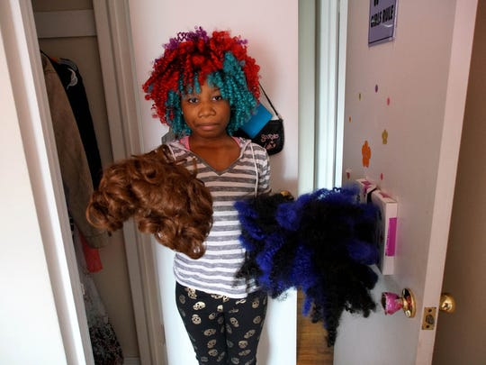 13 year-old Trinity Neal holds a couple of her wigs
