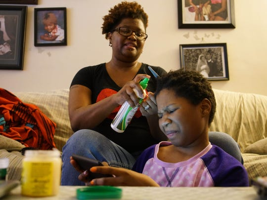 Trinity Neal grimaces as her mother DeShanna sprays conditioner on her hair while braiding it.