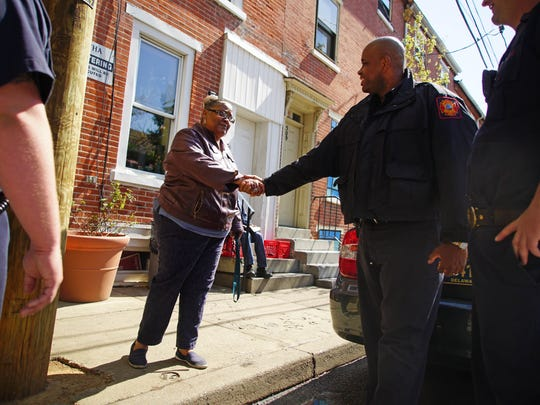 Resident Dee Moore of the 500 block of W. 7th St. shakes hands with firefighter Hiram Whatley with the Wilmington Fire Department and fellow firefighters who were out walking the neighborhood to document safety issues with vacant properties.