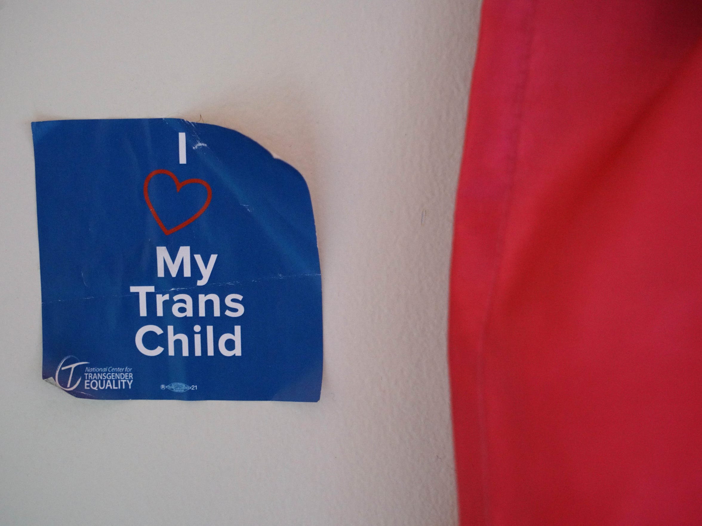 A support for transgender children sticker hangs next to curtains in Trinity's bedroom.