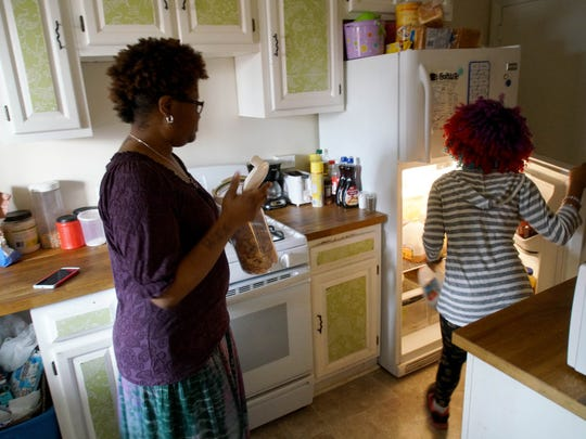 DeShanna helps fix a snack for her 13-year-old transgender daughter.
