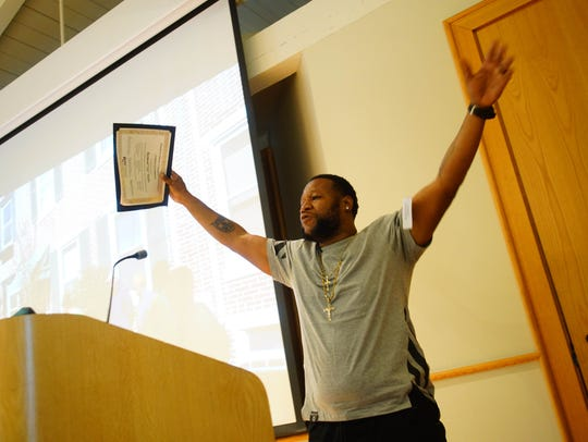 Raymond Taylor holds up his certificate of completion