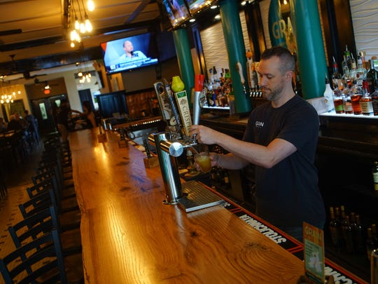 Bartender Joe Ordway pours a beer at the new Grain