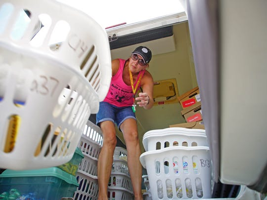 Silver Lake Elementary School Librarian Jodie Klein reloads laundry baskets full of books into the Appoquinimink Bookmobile before heading to Townsend Elementary School to distribute morning books to promote summer reading.