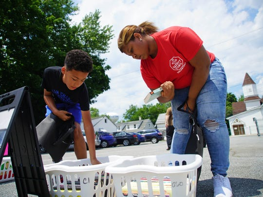 Twelve-year-old Jaiden McGhee, left, and his cousin Akyra Boswell look through books in the parking lot of Dale United Methodist Church on Wednesday afternoon while the Appoquinimink mobile summer library was visiting their neighborhood to promote summer reading.