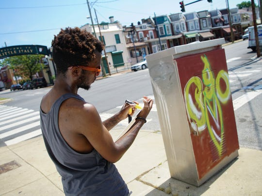 Local artist JaQuanne LeRoy Daniels prepares to paint a mural depicting a variety of peas on the side of an electrical box at Fourth and North Lincoln streets in Wilmington.