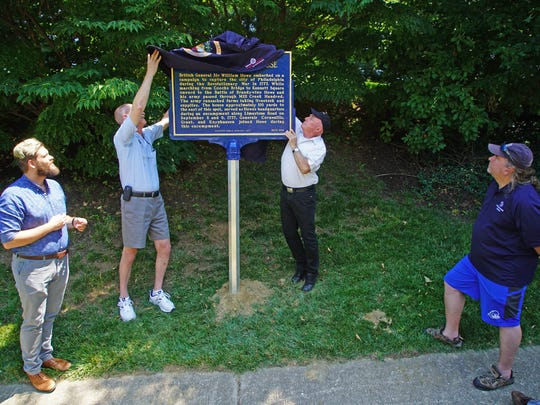 Walt Chiquoine and Joe Lake, both with the Hockesin Historical society, unveil a historic marker marking the spot where the British army camped in Hockessin in the days before the Battle of Brandywine.