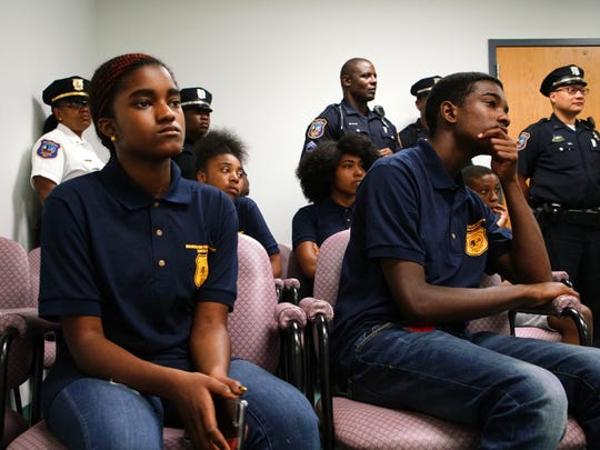 Candice Cardenas and her brother Cornelius Cardenas listen to a judge in the courtroom at the Wilmington Police Department talk about his process for addressing criminal issues.