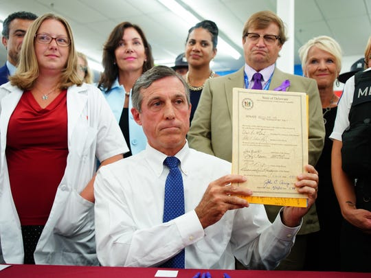 Governor John Carney holds up Senate Bill 48 at CVS in Dover after signing it into law on Thursday. The will make  naloxone, an antidote for those suffering from opioid overdoses, more readily available in pharmacies.