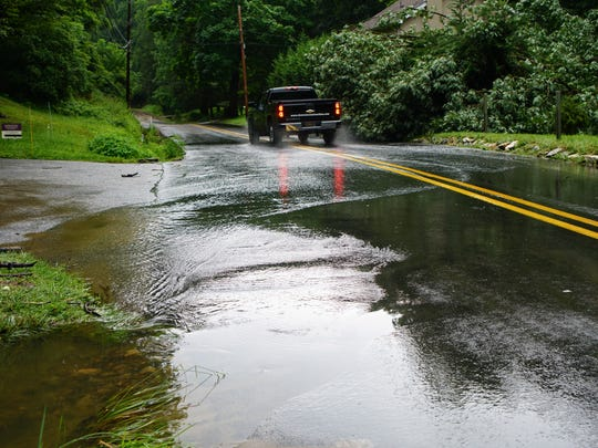 A truck drives along Brackenville Road through flowing water from a nearby clogged storm drain from a July storm that dropped 5 inches of rain on the northern part of Delaware.
