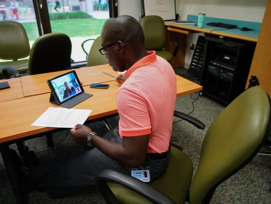 Dr. Alfred Atanda, an orthopedic surgeon at Nemours/A.I. DuPont Hospital for Children, holds a telehealth follow-up appointment with his patient, 16-year-old Abigail Bucklin, of Rehoboth, on his tablet.