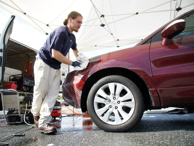 Adam Roberts with On-Site Detailing washes a SUV at