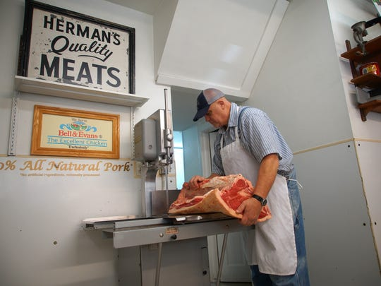 Greg Proffitt, a head meat cutter at Herman's Quality Meats, makes fresh cuts before the store opens for the day.