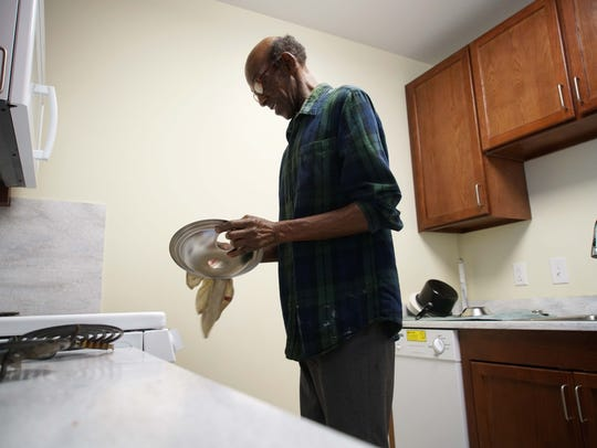 67-year-old Leander Gardner cleans the burners on his stove top in his one bedroom apartment at Sacred Heart Village II.