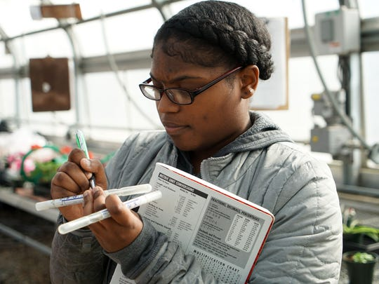 Toddshay Parson, 18, a junior at William Penn William Penn High School, writes down data after swabbing a chicken to learn about bacteria in her microbiology class.