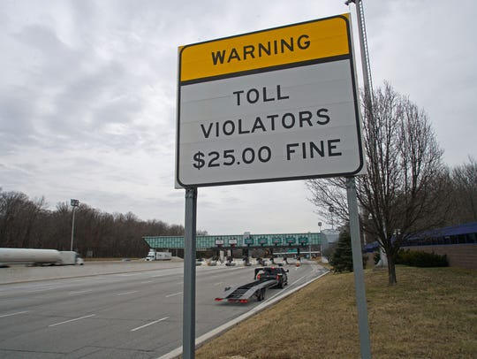Vehicles drive past the toll violation sign at the