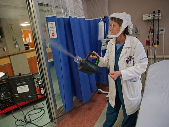 Dr. Sandy Gibney, head of emergency for St. Francis Hospital, demonstrates the SteraMist machine that is used killed flu virus in hard to reach places in the hospital.