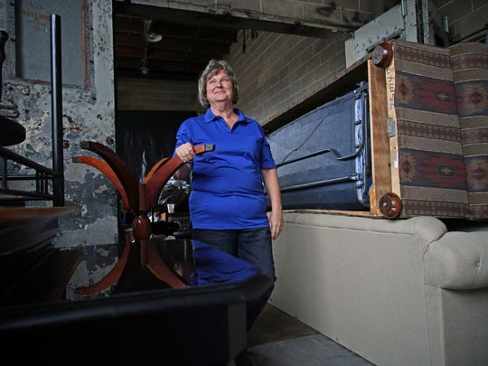 Cheri Collins, vice president of Meet Me at the Well, an organization that delivers furniture and household goods to former prostitutes, stands in a warehouse filled with donated items.