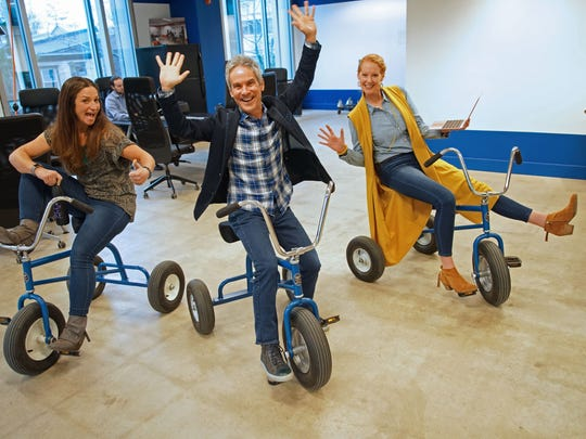 (left to right)Jess Ruggier, ambassador of inclusion, Nick Gianoulis, founder and godfather of fun and Julie Kemple, chief of entertainment officer, for the Fun Department,  a Wilmington-based company that aims to show workplaces how to have fun at work and make happiness at work a reality for various clients, show some fun on tricycles at 1313 Innovation.