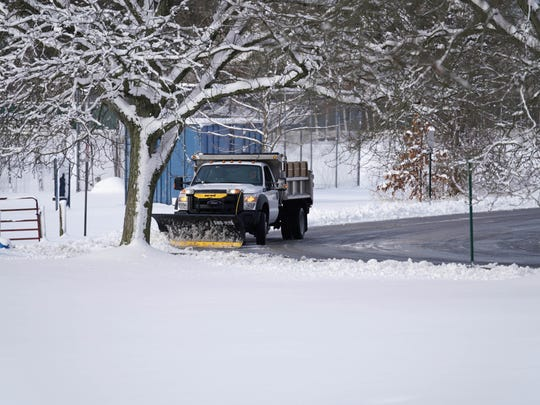 A plow truck removes snow from the parking lot at A.I.