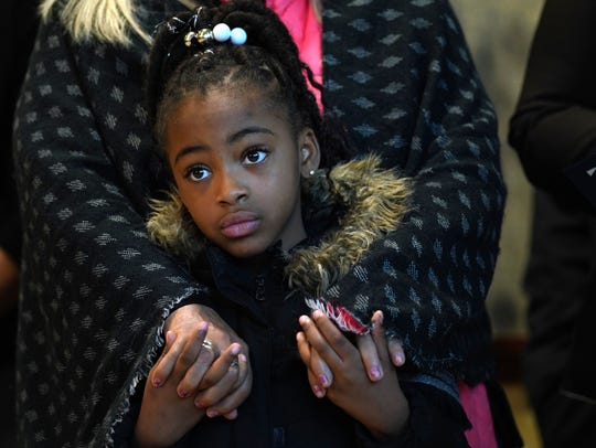 R'Mani Carter, 7, stands wrapped in the arms of her great-grandmother Caren Turner while listening to speakers remember the 50th anniversary of the assassination of Martin Luther King Jr. and the 50th anniversary of the military occupation of Wilmington.