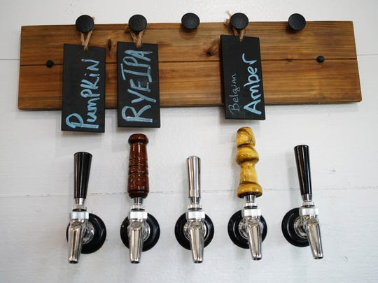 Tap handles with specialty beers made at Kevin Schatz's Middletown microbrewery. He now also offers Harvest Ridge wine, taking advantage of new alcohol rules.