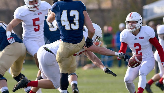 St. John's University's Nathan Brinker blocks a punt by Bethel's Phil Peterson in the first half Saturday at Bethel.