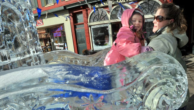 Amy Brown, a parent helper, gives Calissa Salmon, 5, a lift onto the ice throne at the 2013 IceFest. (Public Opinion, Markell DeLoatch)