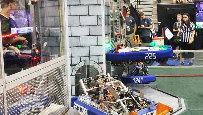 TechFire's 2016 robot, CrossFire, top, climbs up the castle at the end of the match for bonus points. during the Indiana Robotics Invitational last weekend. submitted photo
