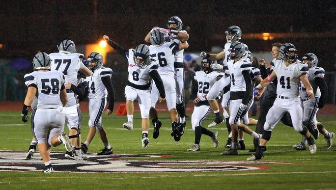 West Clermont players run on to the field after making a goal line stand and defeating Milford 35-28 in the game between the West Clermont Wolves and the Milford Eagles at Milford High School October 27, 2017.