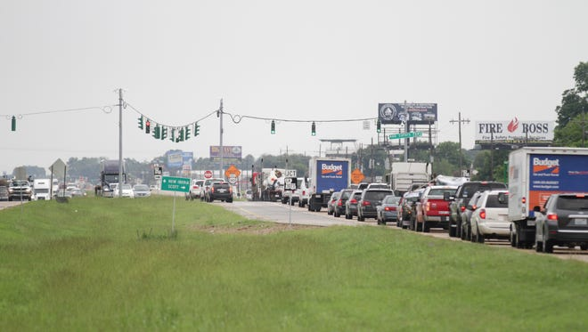 Motorists travel along US Hwy. 90 near its intersection with Ambassador Caffery Parkway in Broussard, La. Thursday, July 17, 2014.