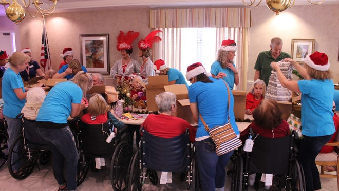 The group opens presents at Highland Manor during a Christmas in July event. Christmas is here and the residents are enjoying Christmas spirit with activities, visitors and decorating.