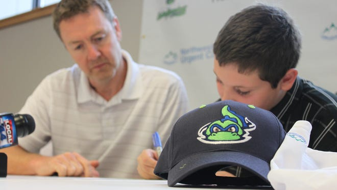 Dakota Brink, right, signes his one-day promotional contract with the Vermont Lake Monsters during a press conference on Friday.