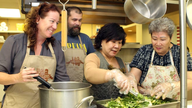 Susan Chapman, director of Loaves and Fishes, works with kitchen volunteers Lance Smith, Incha Sowers, and Song Kim.