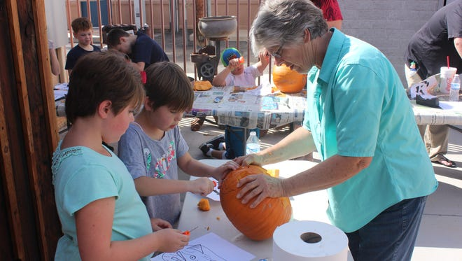 Anya, left, and sister Danna Lindberg carve a pumpkin at the Virgin Valley Heritage Museum with their grandmother Christine Reber.