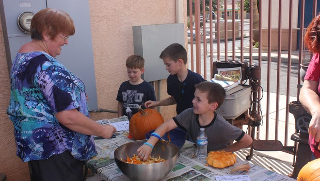 "Elspeth Kuta, Virgin Valley Heritage Museum coordinator, interacts with brothers Asher, Hyrum and Ezra Baker at the ""Pumpkins in the Backyard"" activity held last month."
