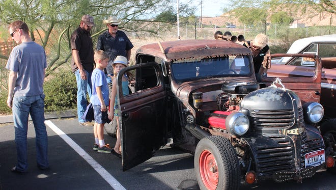 Attendees check out Hal and Deb Allred's Rat Rod Saturday during the car show.