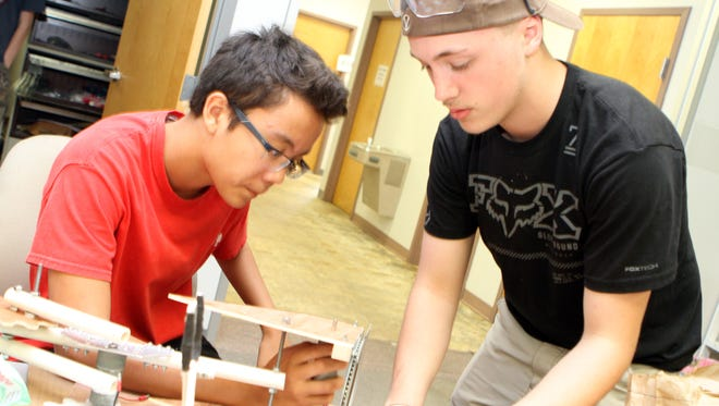 Travis Azure, left, and Chance Peifer, work on the robot's arm, which must be able to rotate 360 degrees and move on multiple axes. The arm will be fitted with a claw that will allow the robot to collect an assortment of objects when Team MARIO competes Saturday at Lipscomb University.