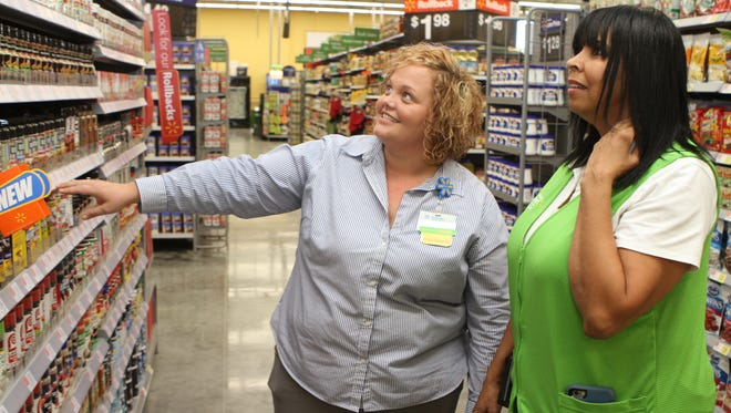 General manager Francies Gardner, left, and General Merchandise Department manager Sharon Shippy, right, put the final touches on the baking aisle of the new Wal-Mart Neighborhood Market on Whitfield Road.