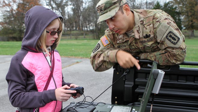 Amanda Bean gets help from Brian Meroni of Fort Campbell's 744th EOD Unit Saturday. Bean is in her third year with the Richview Robotics program. She was the driver for the team's last challenge, the ring hang.