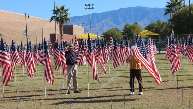 Volunteers set up flags in the Mesquite Recreation Center's field Sunday morning.