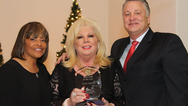 Linda Cappella, center, receives the California Desert Association of Realtors' annual Realtor of the Year award. At left, Beverly Fitzgerald, outgoing CDAR president; and at right, John Gronewold, CDAR CEO.