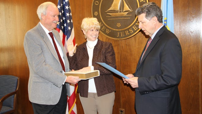 Ocean County Freeholder Virginia Haines is administered the oath of office by county General Counsel John C. Sahradnik (right) with Freeholder Director John C. Bartlett Jr. holding the Bible.