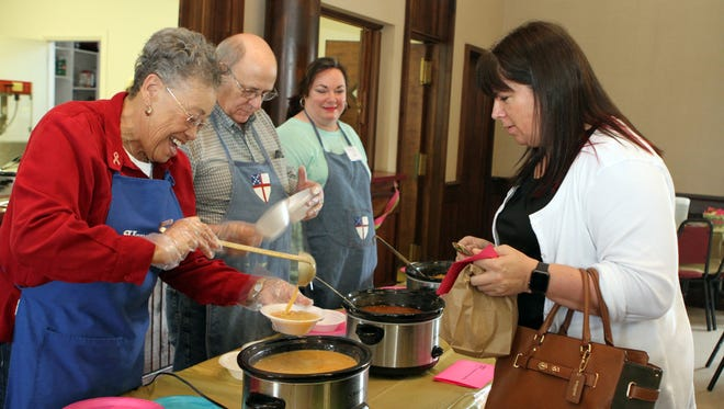 Sharon Mitchell (R) being served some cheddar-potato soup by Margaret Foster (L) at Trinity Episcopal Church, one of six venues for this year's Empty Bowls event. Other volunteers at the venue included John Hilborn and Kate Smith who stayed busy serving 200 guests lunch Tuesday.
