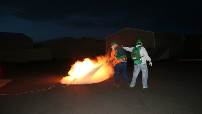 Students Jeff Leach, left, and Don Charpilloz team up to suppress a fire during the CERT training at Salem Fire Station #6 on March 10.